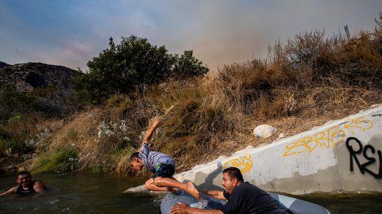 Eddie Lopez e o seu filho, Eddie Jr., brincam perto de uma conduta de drenagem no ...
