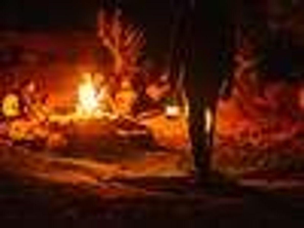 Fotografia de pessoas sentadas à volta de uma fogueira à noite.