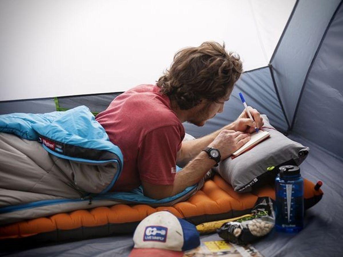 Fotografia de um homem numa tenda a escrever num bloco de notas.