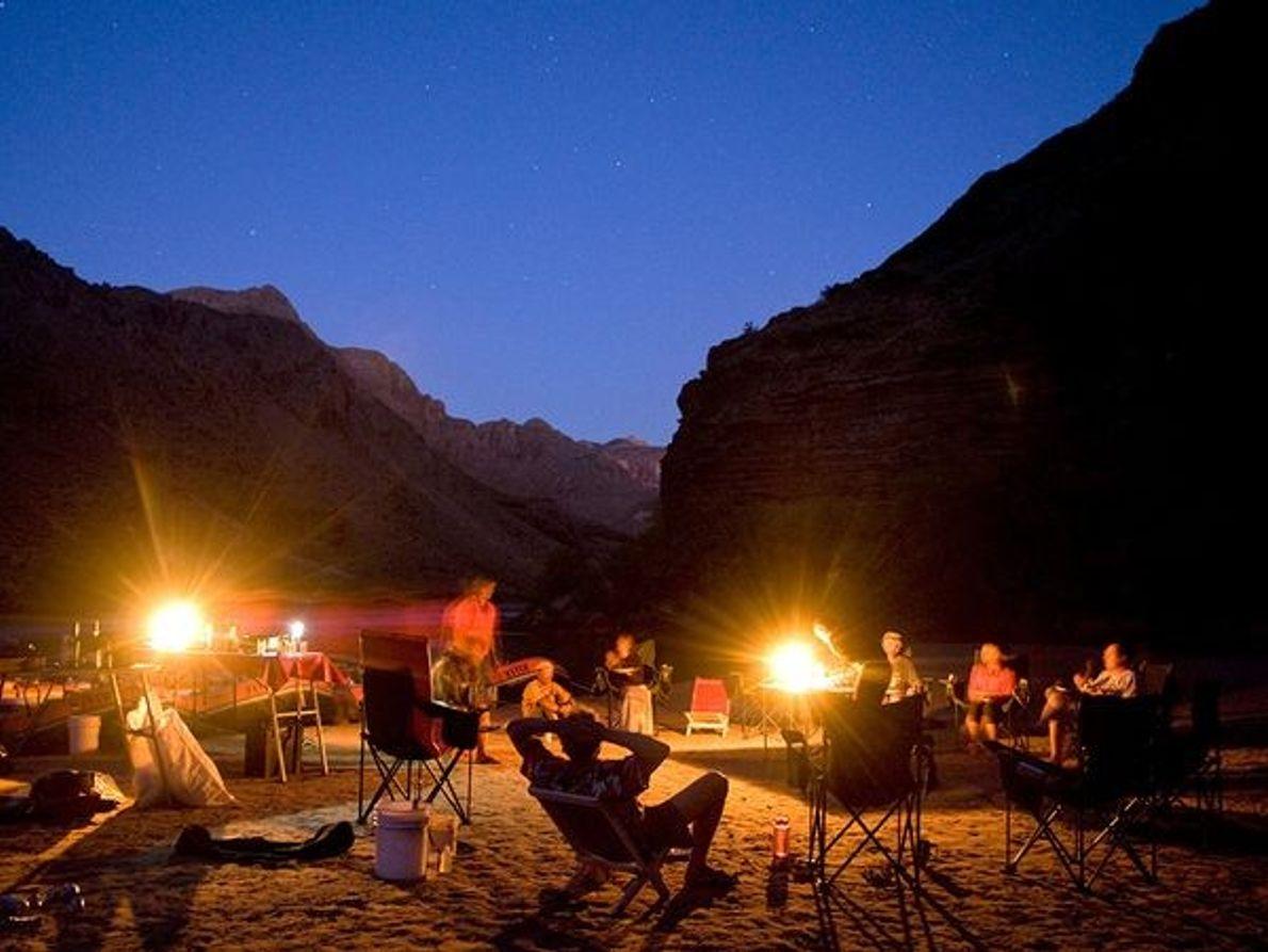 Fotografia de campistas a apreciar a noite à volta da fogueira.
