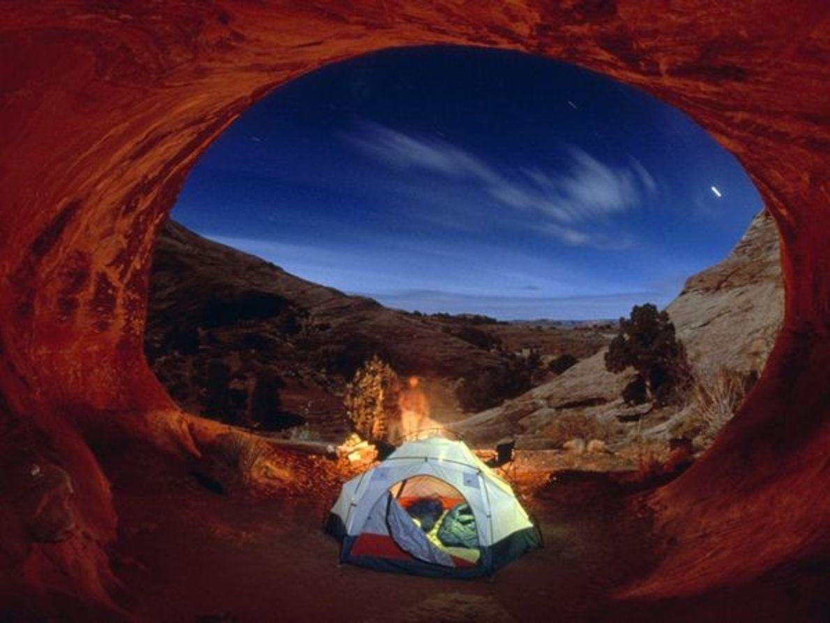 Fotografia de pessoas a acampar debaixo das estrelas no Arches National Park, Utah.