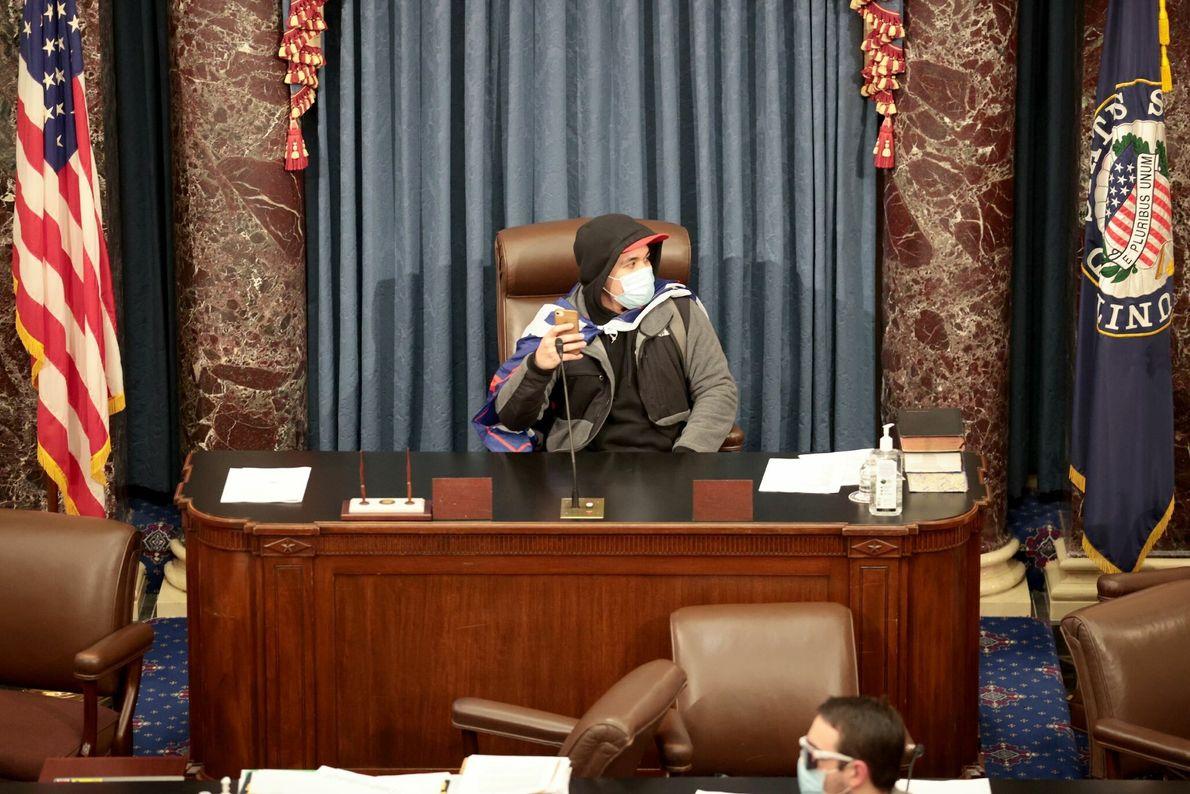 Um manifestante sentou-se na secretária da Câmara do Senado, depois de os legisladores terem interrompido a ...