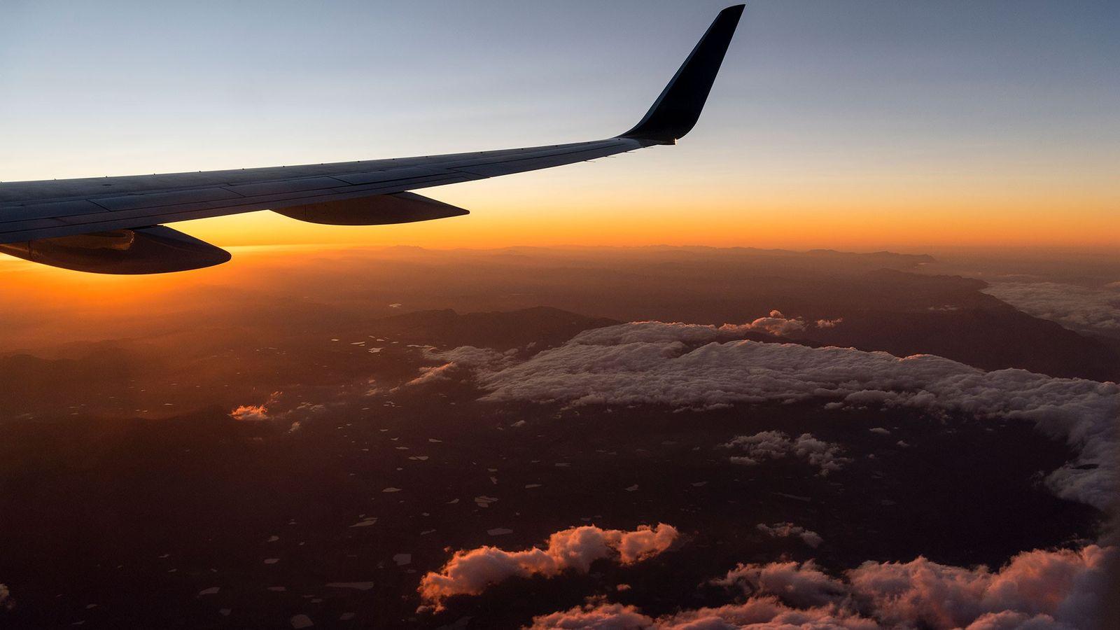 A asa de um jato voa sobre um amanhecer quente na Cidade do Cabo, na África ...