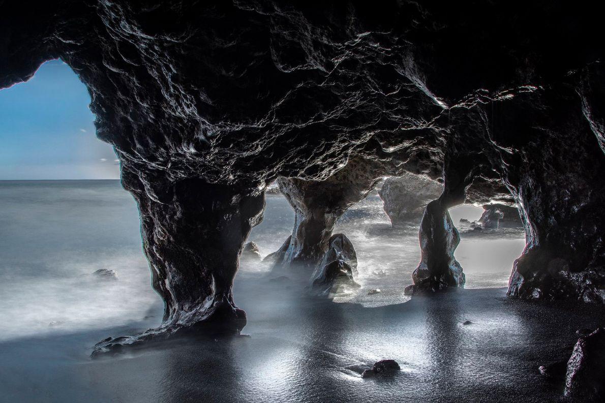 Uma explosão de luz solar delineia as paredes das cavernas de calcário, numa praia das Ilhas ...