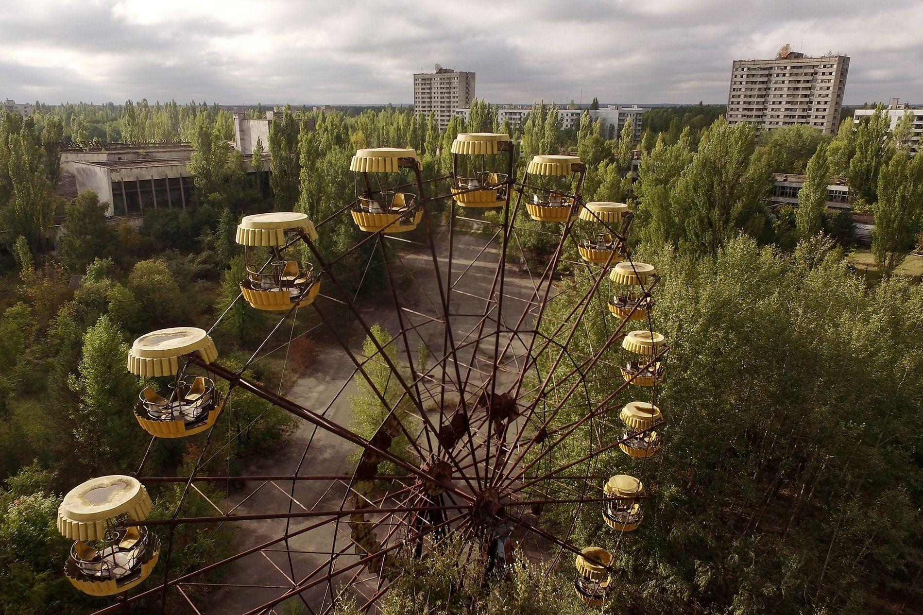 A roda de um parque de diversões permanece abandonada.