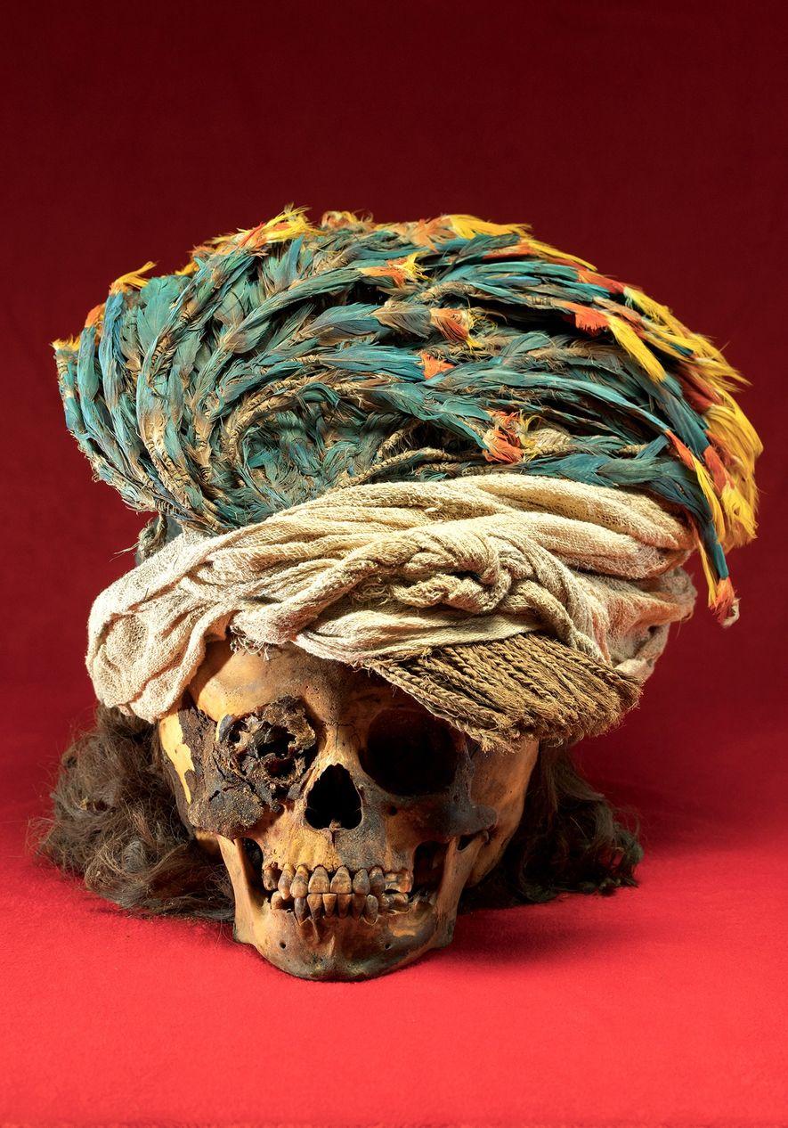 Um ornamento de penas de arara adorna o crânio de uma criança sacrificada. Os investigadores dizem ...