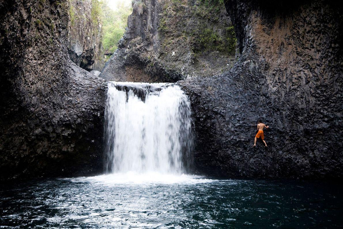 Homem escala a parede rochosa de uma pequena cascata