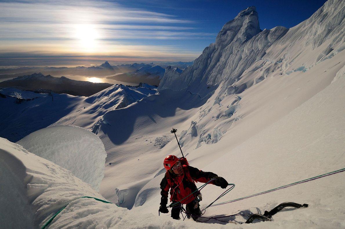 Montanhista sobe ao topo de uma montanha coberta de neve