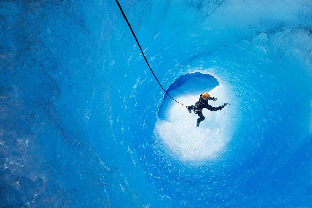 Um escalador de gelo sobe a parede de uma gruta