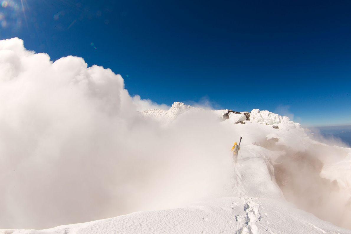 Esquiador transporta o seu equipamento pelo meio de uma nuvem