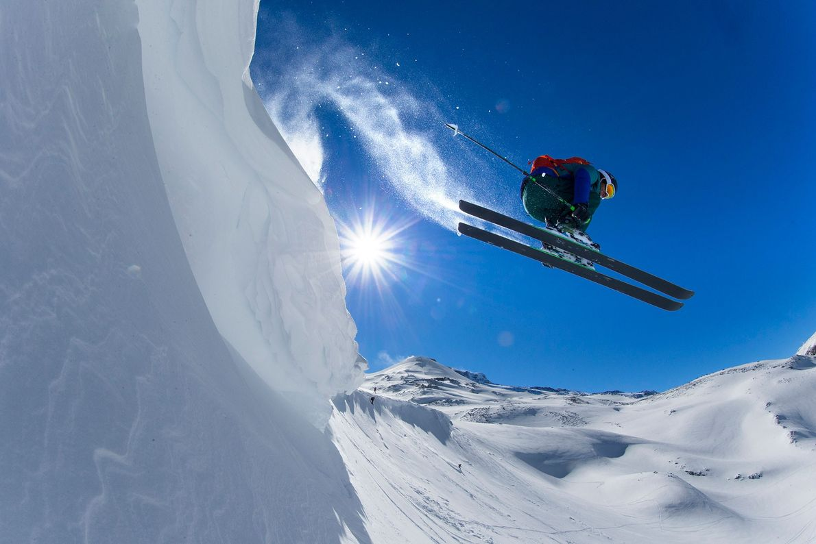 Esquiador lança-se de um cume numa estância de esqui