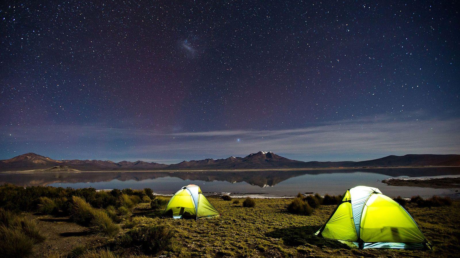 Duas tendas iluminadas sob um céu estrelado em Salar de Surire