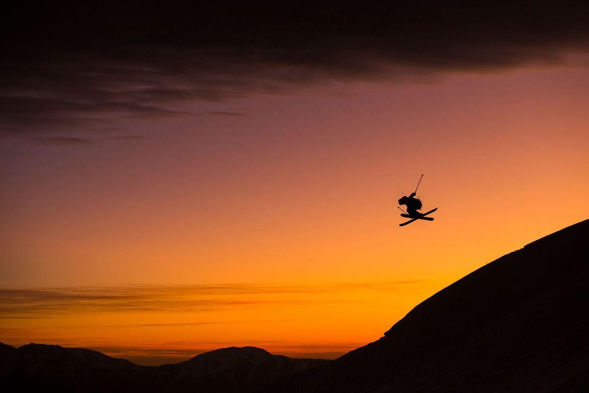 Esquiador salta do topo de uma montanha numa estância de esqui
