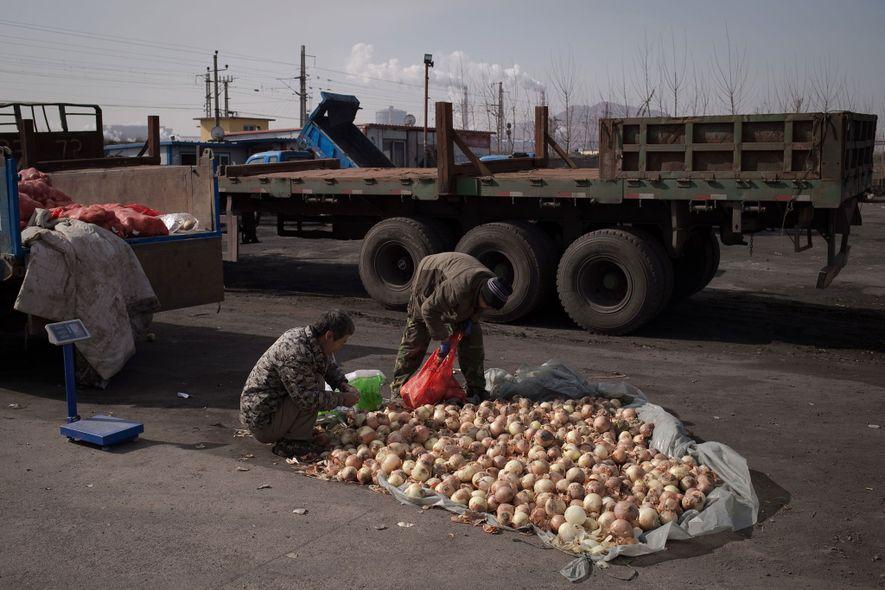 Vendedores embalam cebola em sacos para ser vendida no mercado em Tangshan. Apesar de a indústria ...