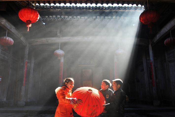 As crianças ajudam a mudar as lanternas para o próximo ano num edifício antigo na vila ...