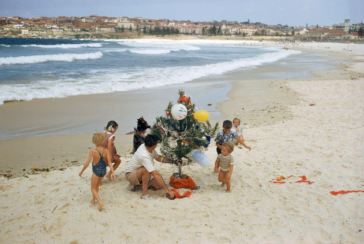 Uma família australiana decora uma árvore de Natal na praia Bondi, em Sydney, em 1956.