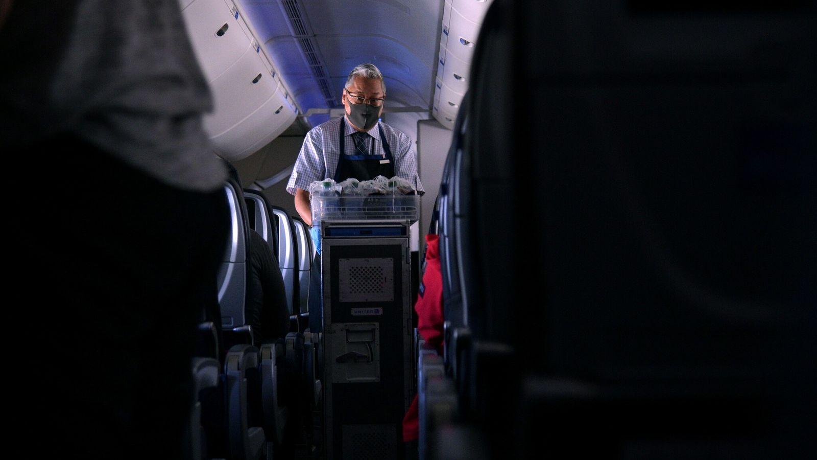 Um comissário de bordo com máscara distribui águas e refrigerantes num voo de São Francisco, na ...