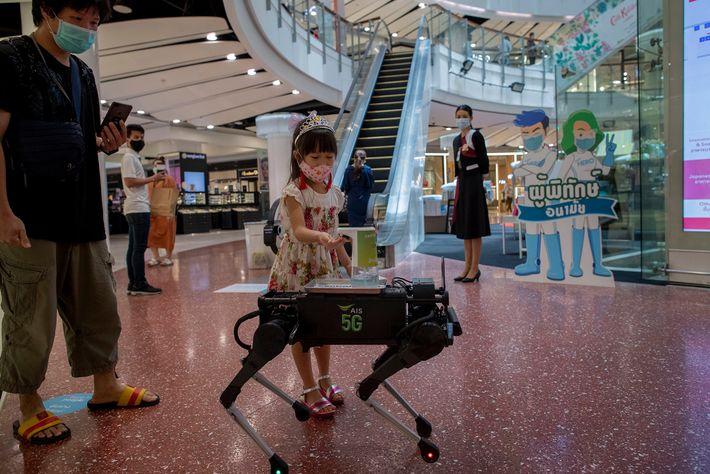 Uma menina desinfeta as mãos com desinfetante dispensado por um robô que anda pelo Central World, ...