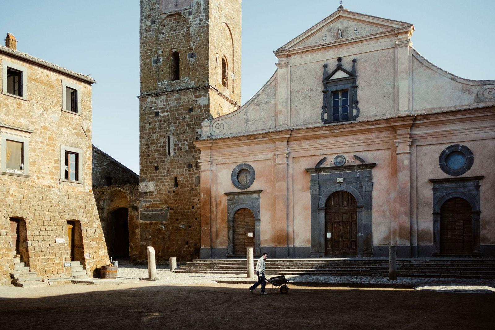Um homem a empurrar um carrinho de mão na praça central de Civita, em frente à ...