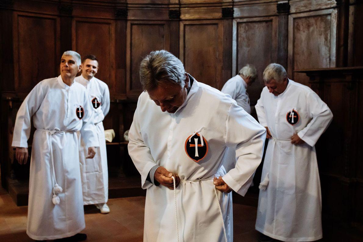 A confraria de Civita veste as suas capas brancas tradicionais em preparação para a missa e ...