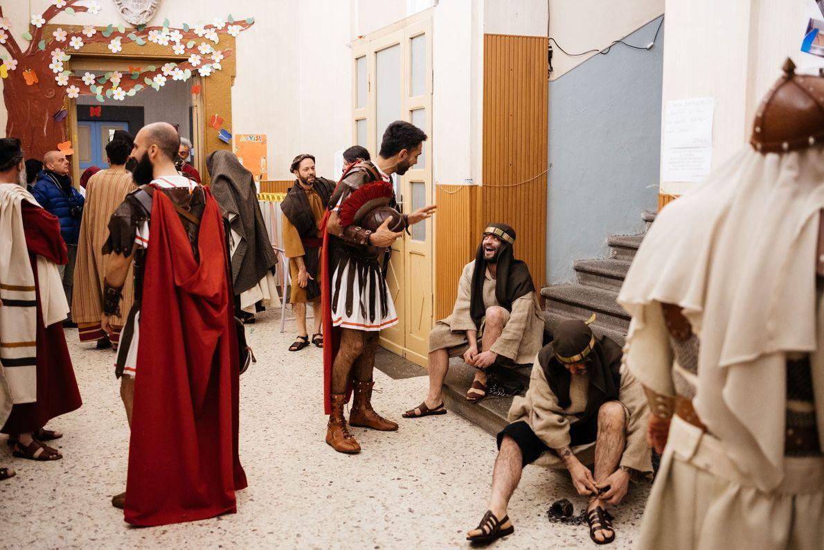 Vestidos a rigor com trajes históricos, os voluntários conversam momentos antes do início da procissão.