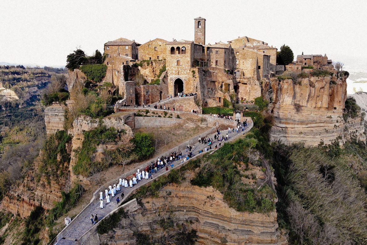 Vestidos de branco, os membros da fraternidade religiosa de Civita levam os turistas e habitantes locais ...