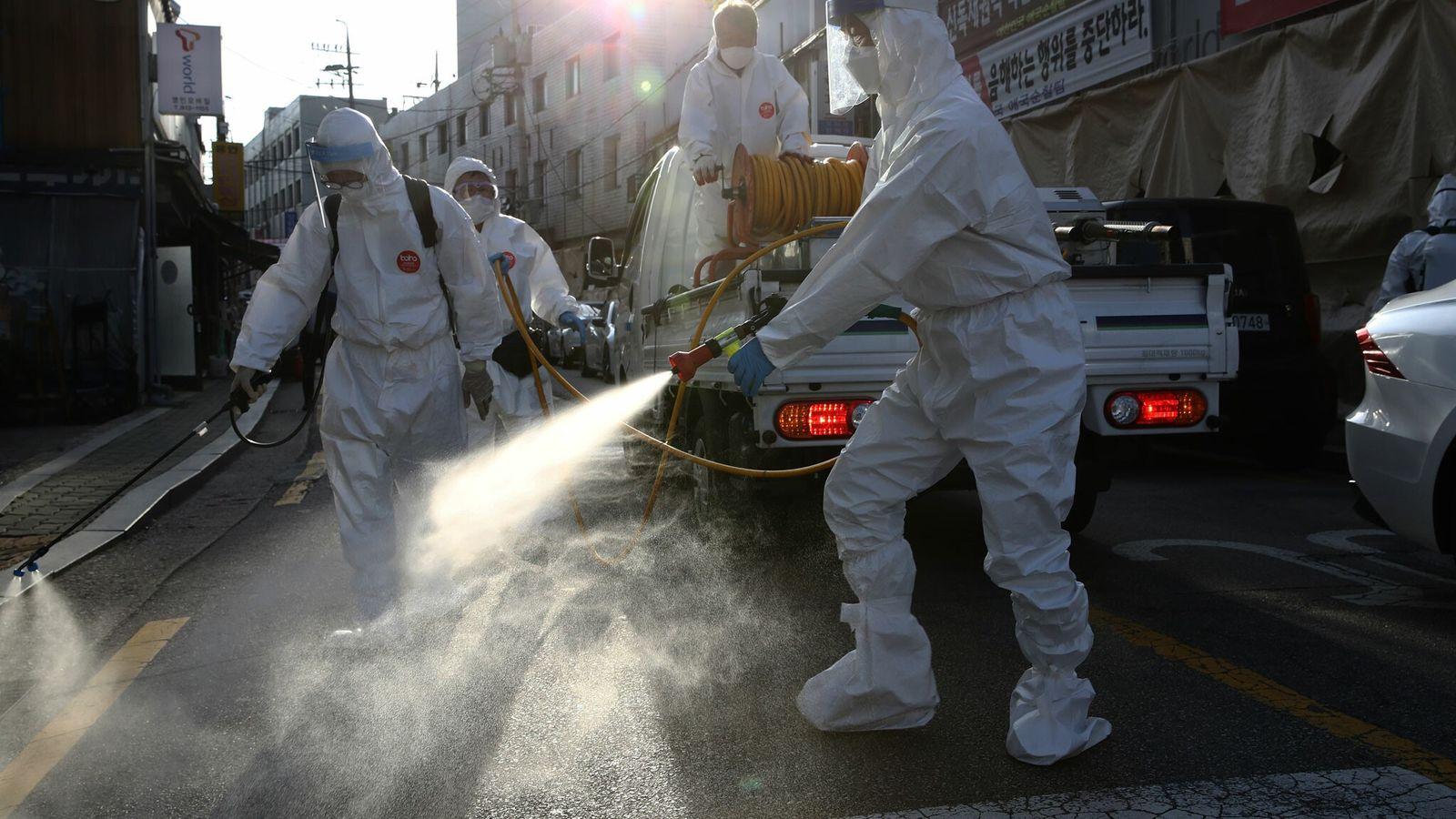 Trabalhadores com equipamento de proteção individual desinfetam uma rua para evitar a propagação de coronavírus, no ...