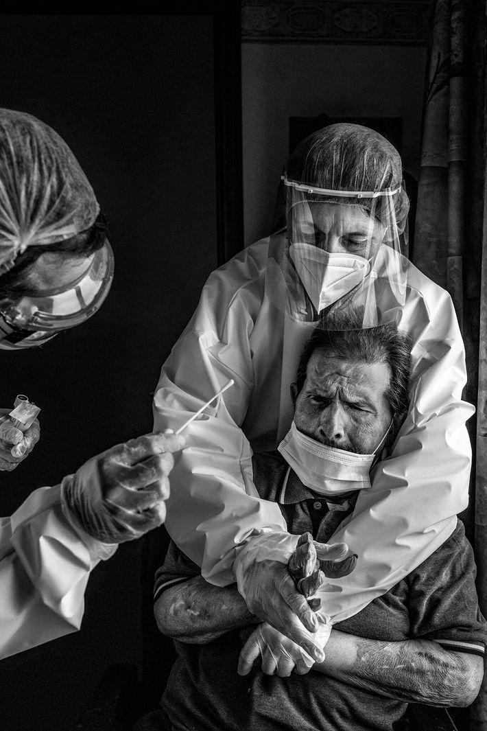 Numa casa de repouso em La Louviere, na Bélgica, uma enfermeira estabiliza um residente para o ...