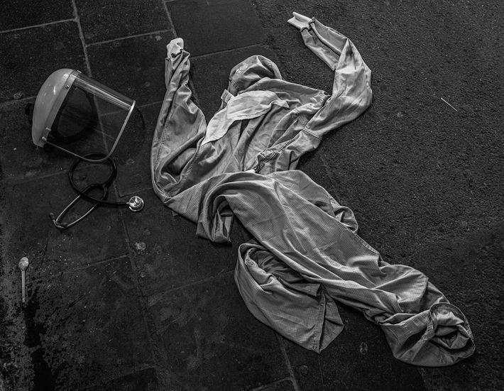 O equipamento de proteção individual (EPI) de um médico está espalhado no chão, no exterior de ...