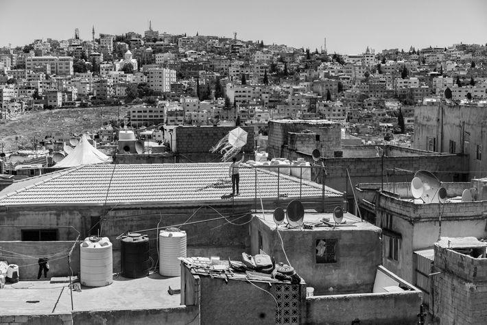 Durante o confinamento em Amã, um jovem da Jordânia brincava com um papagaio num telhado. As ...