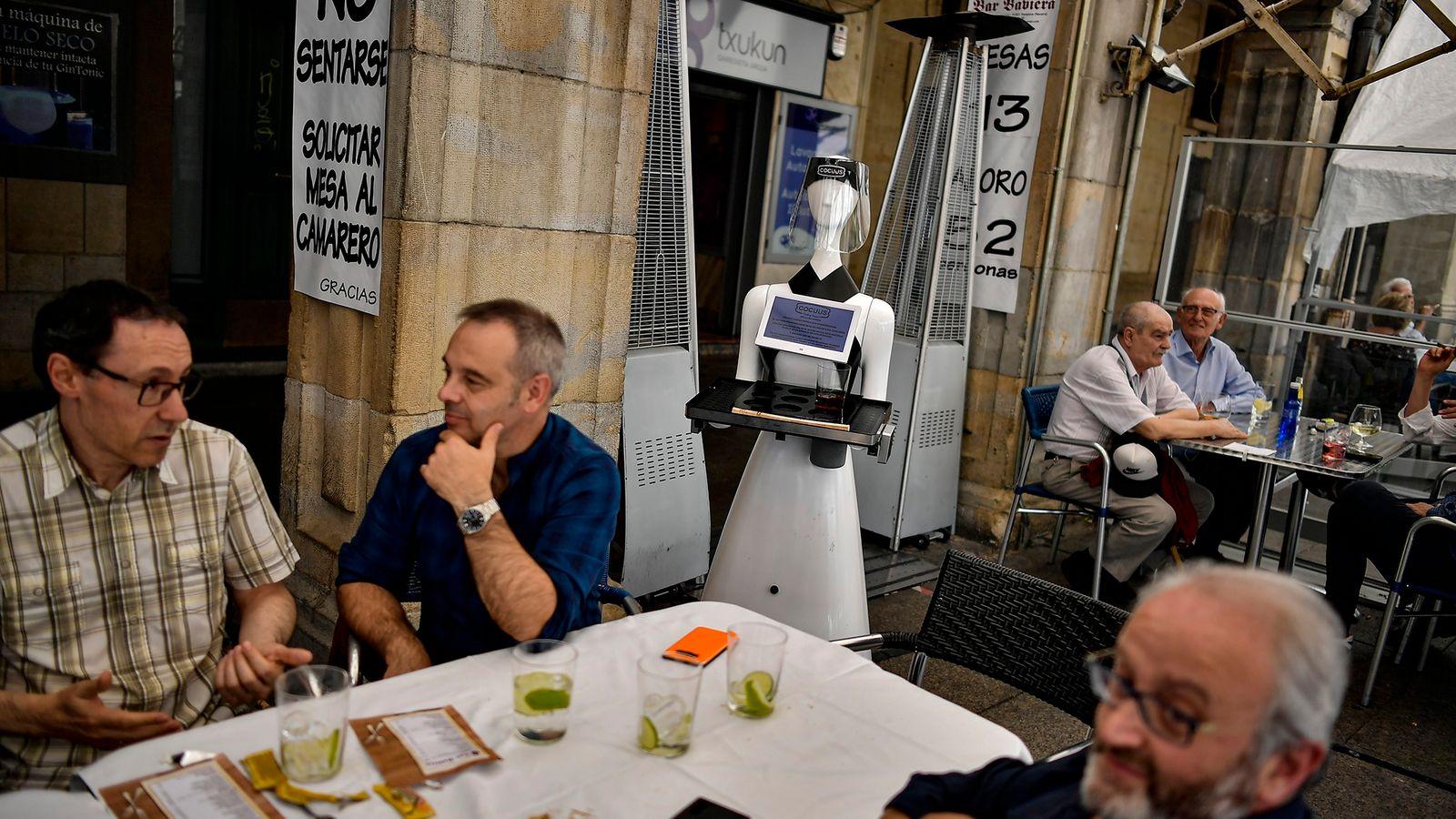 Usando uma viseira para mostrar espírito de equipa devido à COVID, um robô de 1,5 metros ...
