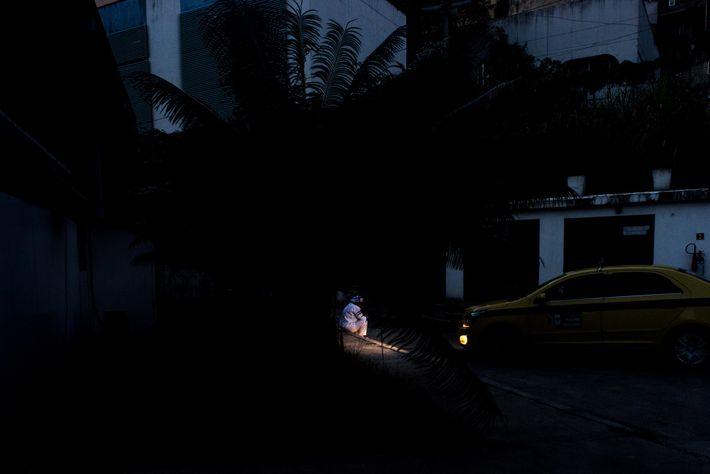 Uma profissional de saúde durante o período de pausa é iluminada pelos faróis de um táxi ...