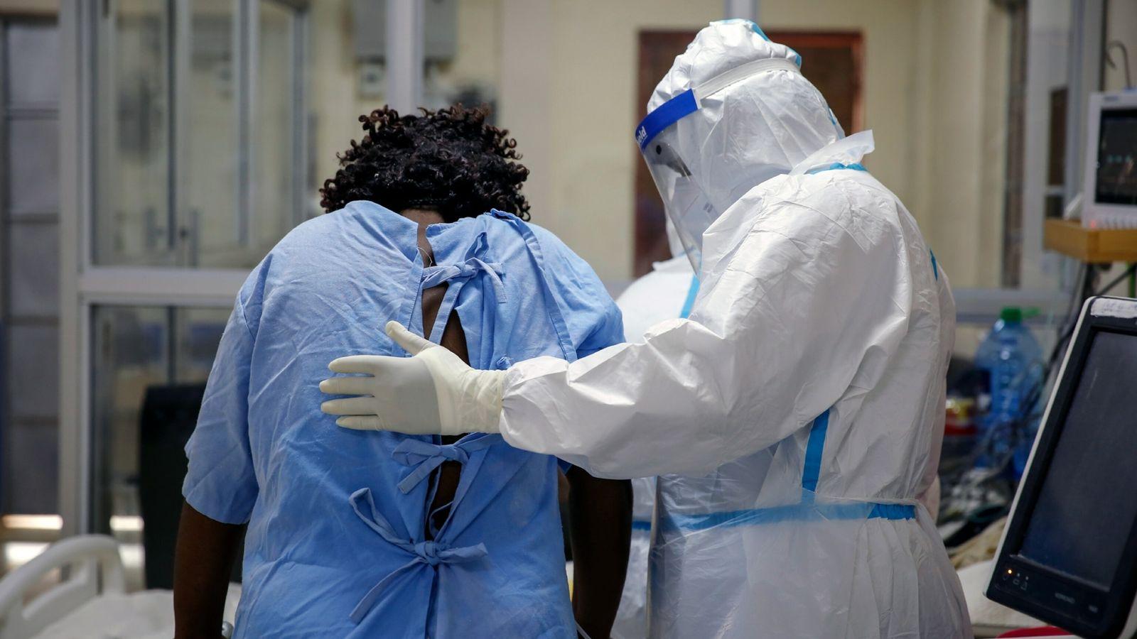 Um profissional de saúde cuida de um paciente com coronavírus na unidade de cuidados intensivos de ...