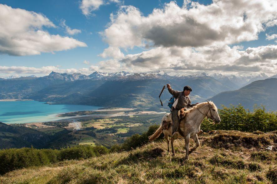 Um agricultor a cavalgar, com o Lago General Carrera como pano de fundo, perto de Puerto ...