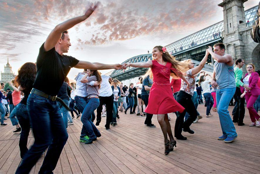 Moradores e visitantes a dançar numa plataforma à beira-rio, no Parque Gorky de Moscovo, onde as ...
