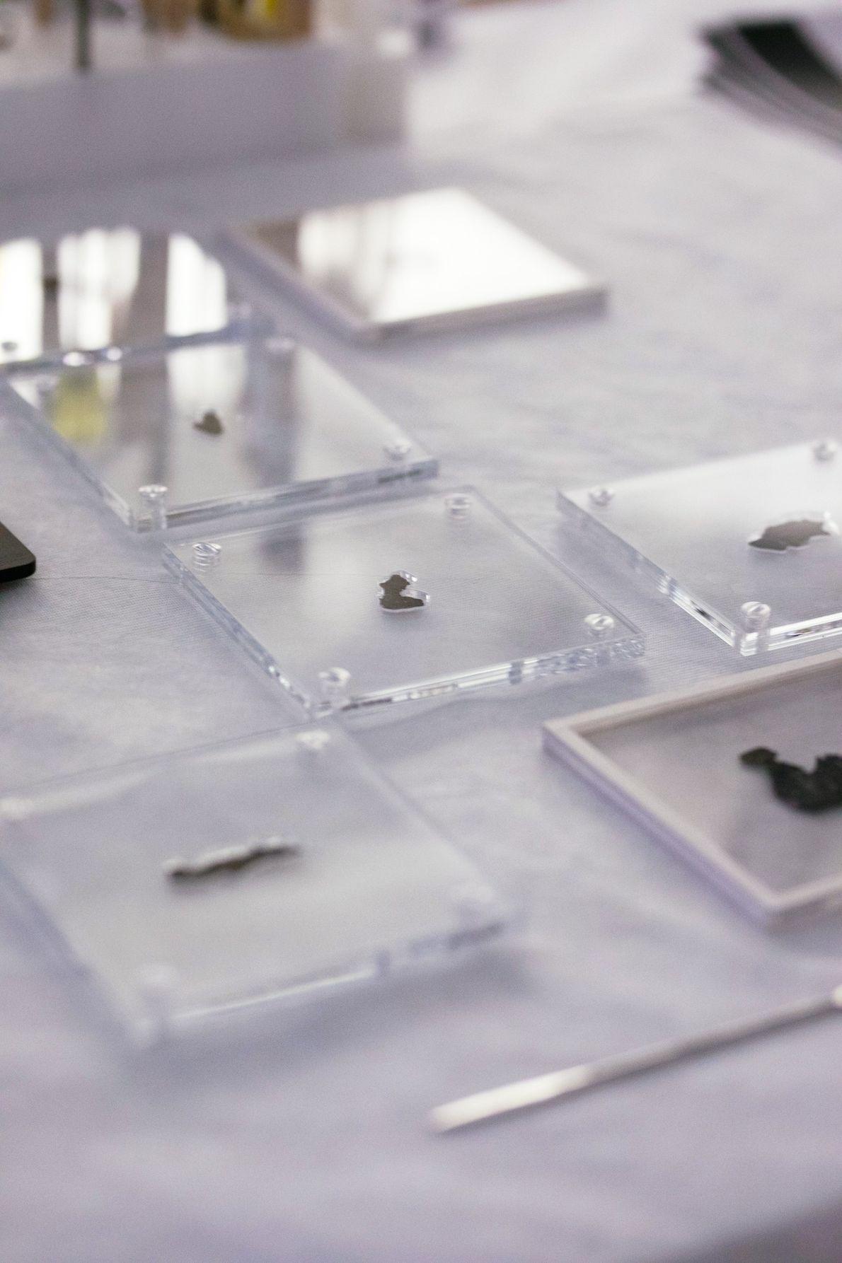 Protegidos em invólucros de acrílico personalizados, os fragmentos dos Manuscritos do Mar Morto do Museu da ...