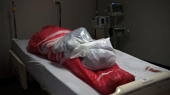 Um homem que morreu devido ao coronavírus é visto embrulhado num saco, na unidade de cuidados ...