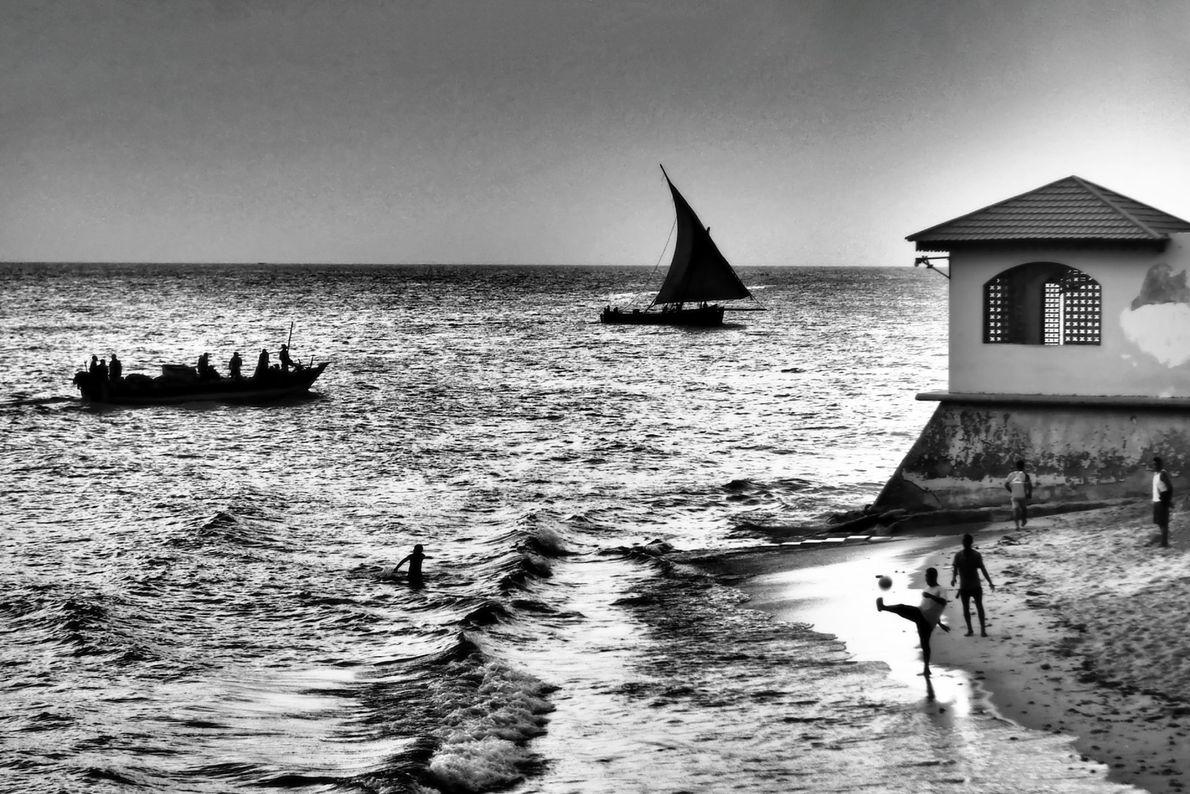 Marinheiros, velejadores, e pessoas a jogar futebol aproveitam o clima ensolarado da praia nos arredores de ...