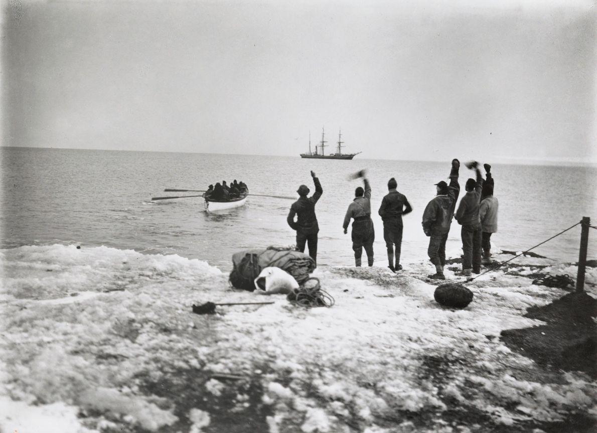 Membros da expedição polar de Robert Falcon Scott estão na praia e acenam para os camaradas ...