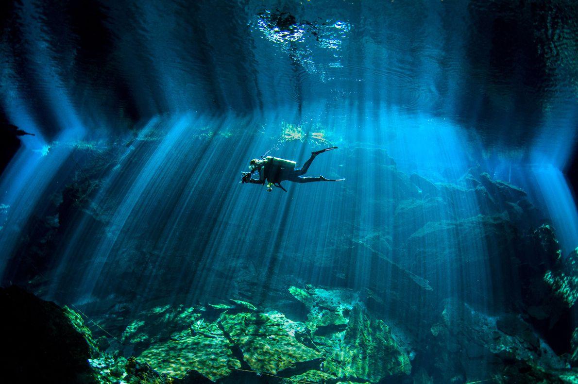 Um mergulhador nada no cenote de Chac Mool, no México.