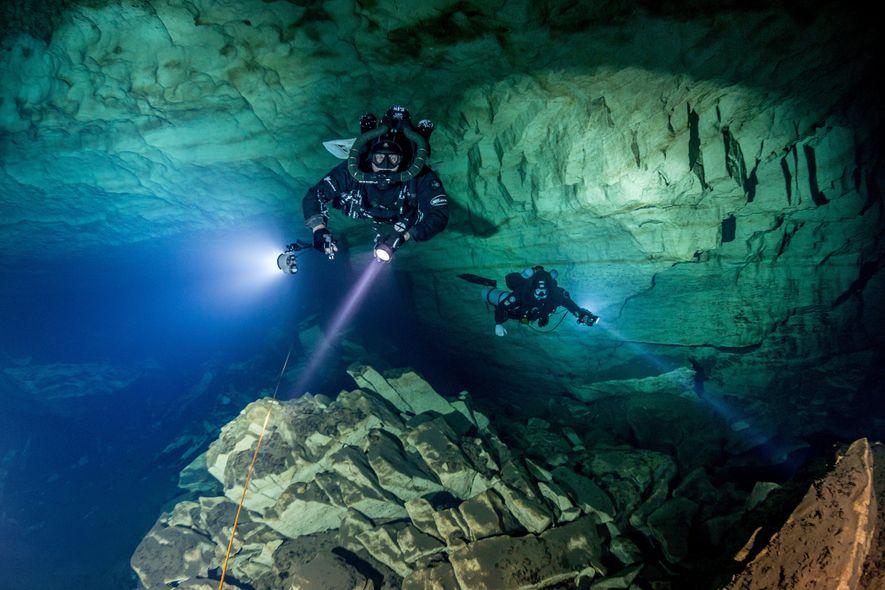 Mergulhadores nadam através de grutas subaquáticas, a mais de 90 metros de profundidade, no Eagle's Nest ...