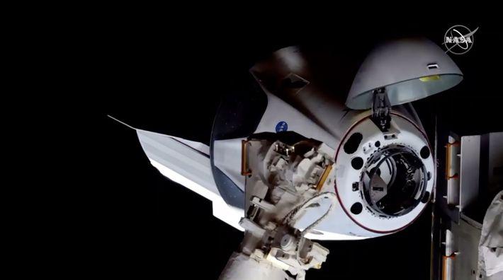 Com a zona frontal aberta para acoplar, a cápsula Crew Dragon da SpaceX chegou com sucesso ...