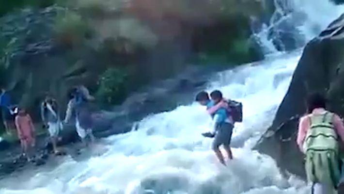 Para ir al colegio, estos niños deben atravesar las aguas turbulentas de un río