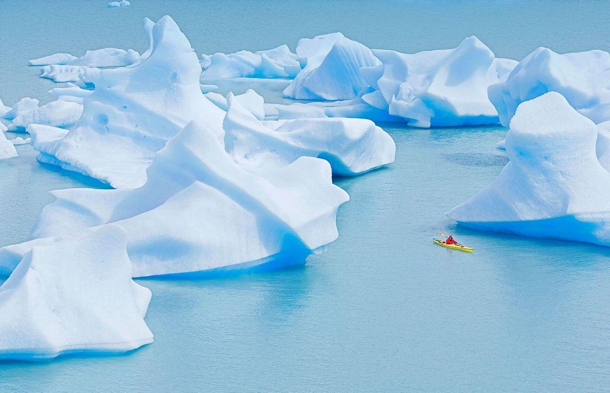 Um canoísta rema junto a icebergues incríveis, no Lago Gray, no Parque Nacional Torres del Paine, ...