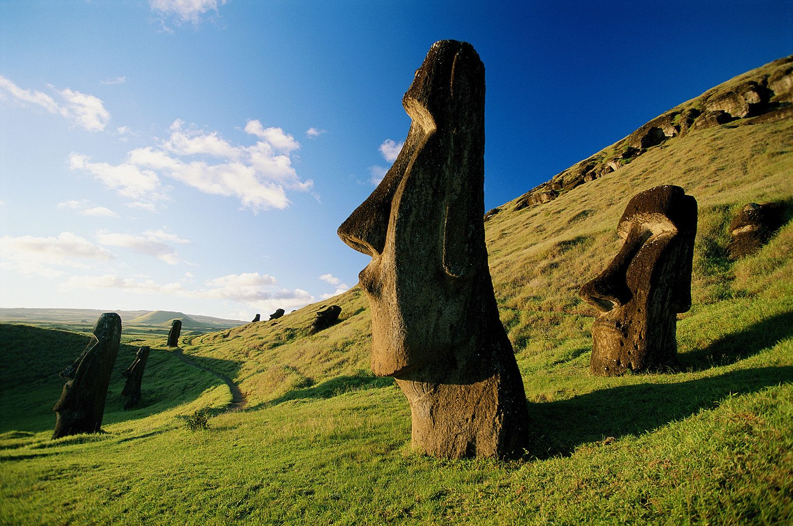Esculturas moai pontilham as encostas verdejantes da Ilha de Páscoa.