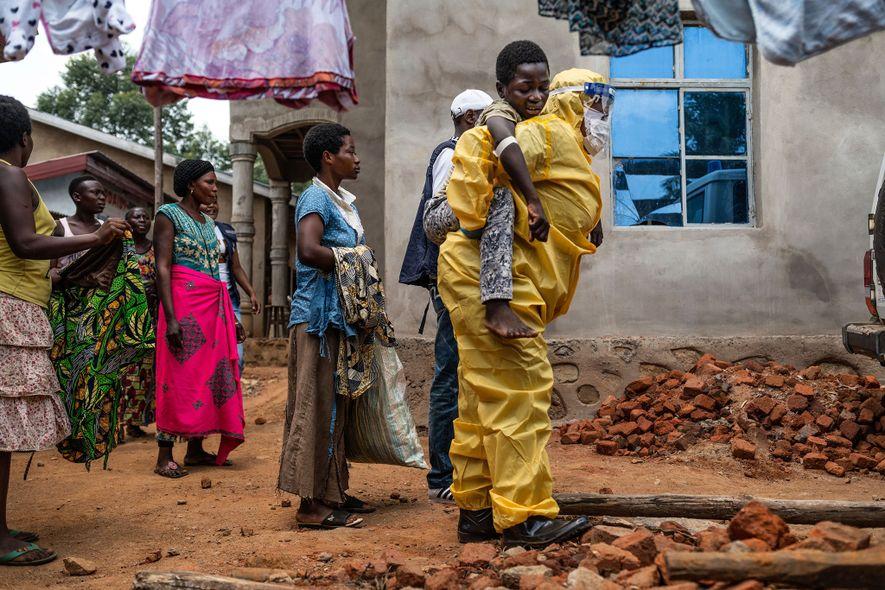 Um profissional de saúde leva Kakule Kavendivwa, de 14 anos, para uma ambulância em Beni. No dia anterior, as irmãs de Kakule tinham-no levado a um centro de saúde nas proximidades, mas fugiram quando a equipa as encorajou a levar o irmão para um centro de tratamento. O centro de saúde alertou a Organização Mundial de Saúde para encontrar a família. Depois de várias horas de conversa com os agentes comunitários, acabaram por permitir que Kakule fosse levado de ambulância para o tratamento.
