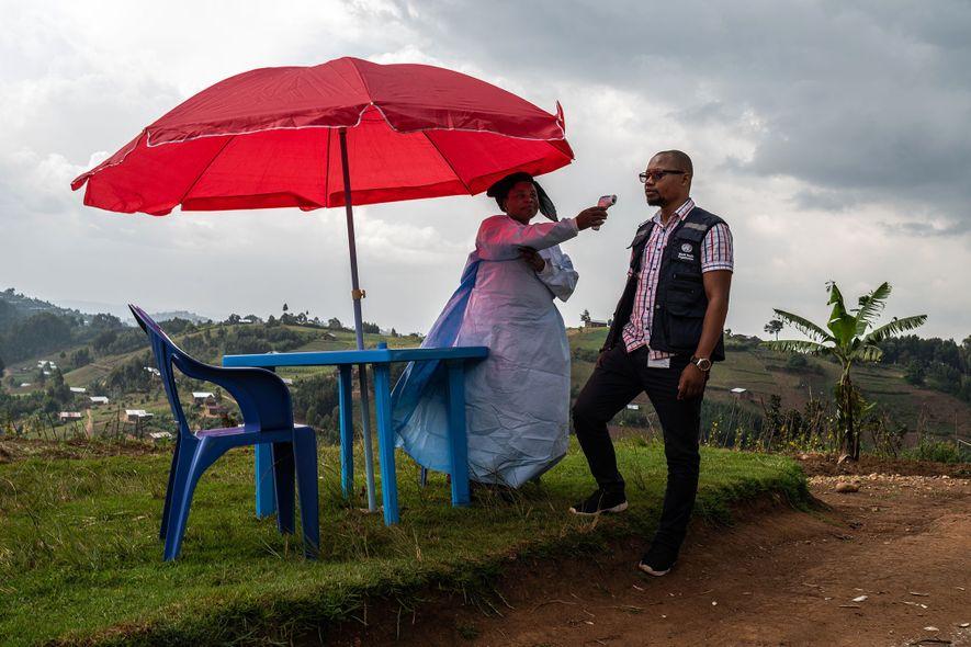 Os profissionais de saúde verificam a temperatura de todas as pessoas que entram na clínica de Vayana, nos arredores de Kyondo. Monitorizar a temperatura das pessoas em hospitais, postos de controlo e postos fronteiriços é uma das ferramentas usadas para acabar com as cadeias de transmissão e controlar os surtos de Ébola.