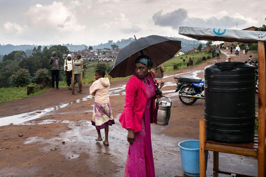 Uma mulher faz uma pausa para lavar as mãos com uma solução de cloro, depois de ...