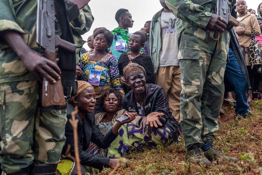Amigos e familiares do agente Tabu Amuli Emmanuel durante o seu enterro, no cemitério Kitatumba, em Butembo.