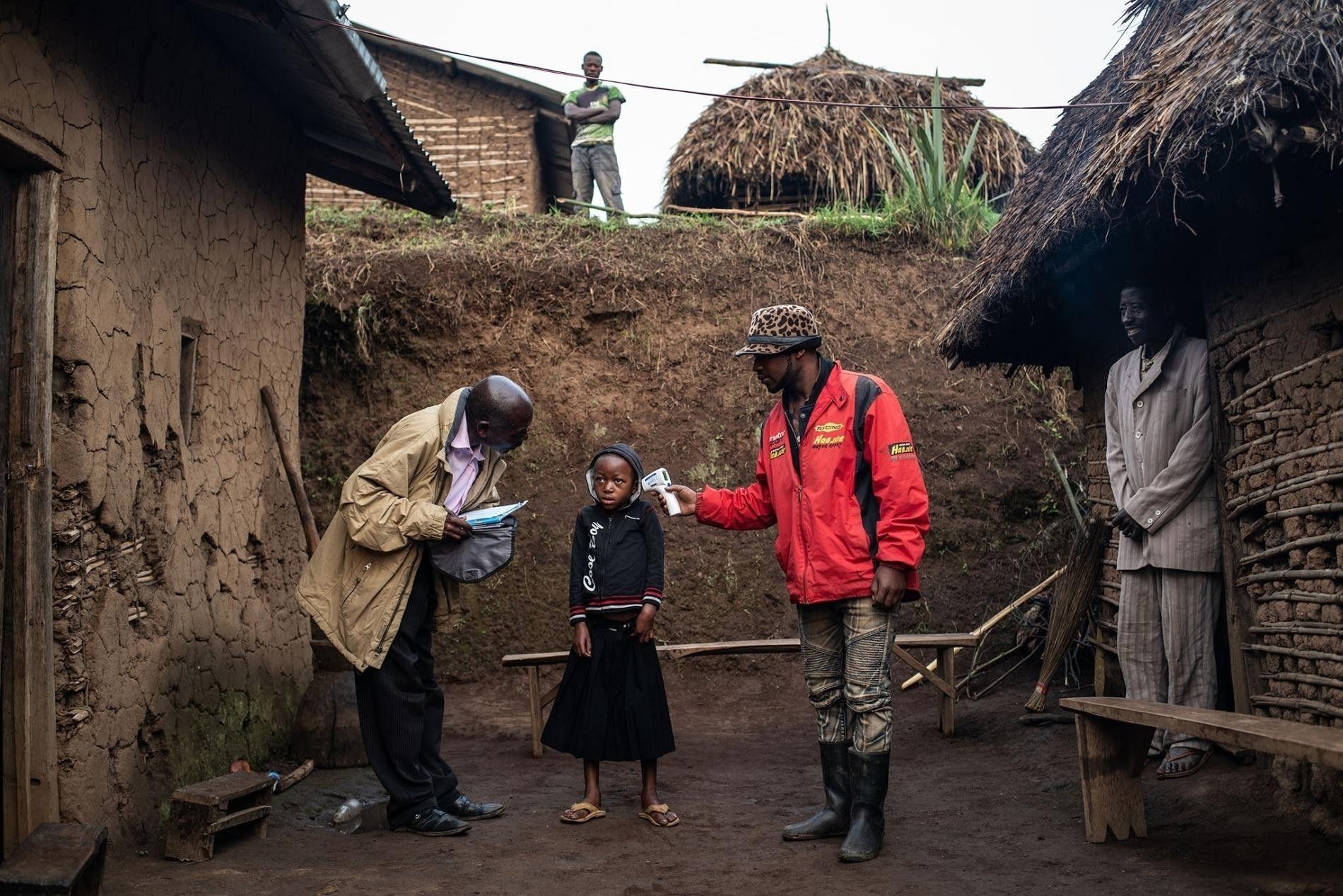 Uma equipa da Organização Mundial de Saúde verifica a temperatura de Masika Mughanyira, de 7 anos, em Vayana, uma pequena vila a duas horas de Butembo, na República Democrática do Congo. Masika perdeu ambos os pais, o irmão mais velho e a irmã mais nova para o Ébola. Agora é a única sobrevivente da sua família e está ao cuidado de parentes.